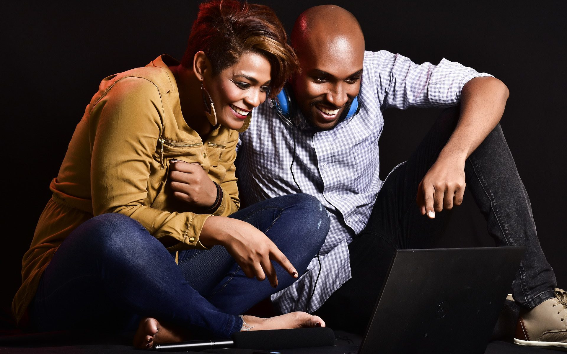 woman and man sitting in front of computer smiling